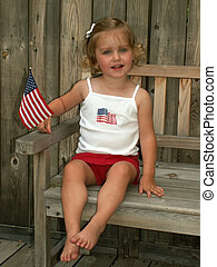 Fourth of July girl - little girl with flag - soft focus -...