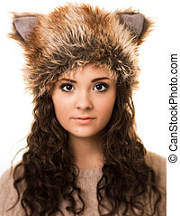 Portrait of a beautiful brunette woman with curly hair and brown eyes wearing a funny fox hat isolated against a white background