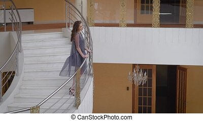 Foyer of the smart hall. Huge ladders, marble floor, beautiful chandeliers. The girl model poses on a ladder. The fair-haired girl in a dress of average length and high-heeled.