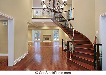 Foyer with balcony and curved staircase - Cherry wood foyer ...