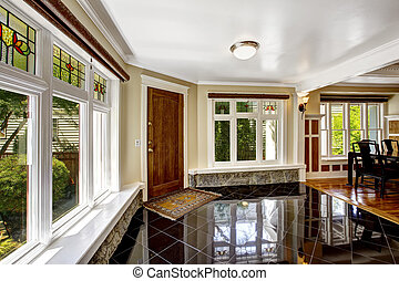 Foyer with black shiny tile floor and stone trim under the...