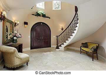 Foyer with curved staircase - Foyer in luxury home with ...