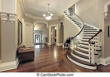 Foyer with curved staircase - Foyer in traditional suburban...