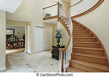 Foyer with curved staircase - Foyer in suburban home with...