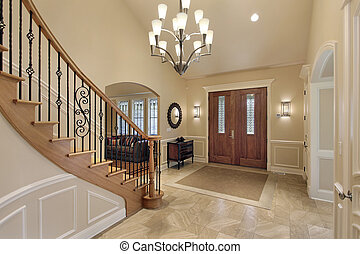 Foyer with curved staircase - Foyer in luxury home with...