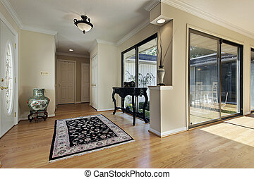 Foyer with doors to courtyard - Foyer in suburban home with...