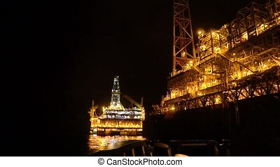 FPSO tanker vessel near Oil platform Rig at night. Offshore oil and gas industry