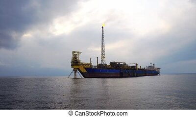 FPSO tanker with burning flare boom. Oil and gas industry...