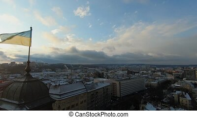 FPV drone flies over the roof of the Lviv Opera and Ballet Theater at sunset. Ukraine flag in the center of the frame. Aerial view of the historical center of Lviv