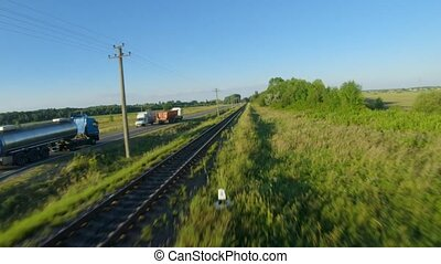 FPV drone flies quickly and maneuverable along the road on which the trucks are riding. Railway is located near the road
