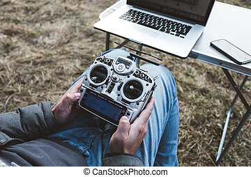 fpv drone pilot. A man sits in a chair with a remote from the FPV drone in front of a laptop and controls the copter. Racing aircraft. Racing copter. Men's hands with a racing copter remote control.