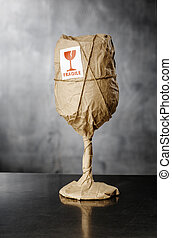 Fragile Contents - A Wine glass packaged in brown wrapping ...