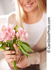 Fragile flowers - Close-up of smiling female holding bunch...