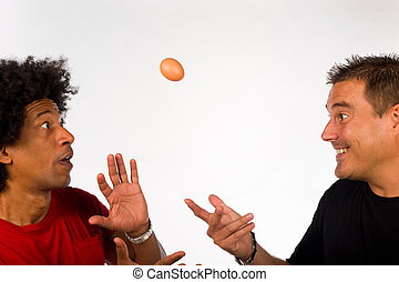 Fragile - Two guys fooling around with an uncooked egg