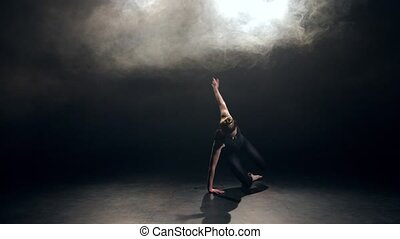 Pretty young actress in black leotard performing gentle dance elements of modern contemporary choreography in smoky backlit studio. Elegant woman dazzlingly dancing in dusk against black background