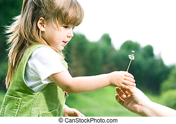 Profile of cute girl taking white dandelion from her parent�s hand on background of green trees