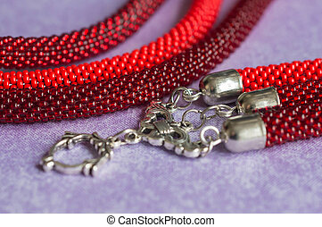 Fragment of a beaded necklace of red color with the lock