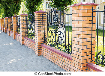 Fragment of a brick fence with forged grille