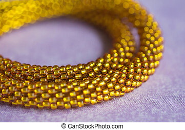 Fragment of a brilliant yellow necklace from beads close up