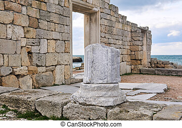 fragment of a column among the ruins of antique greek temple on the seashore