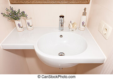 Fragment of a luxury bathroom. Exclusive modern white bathroom with white sink and faucet.