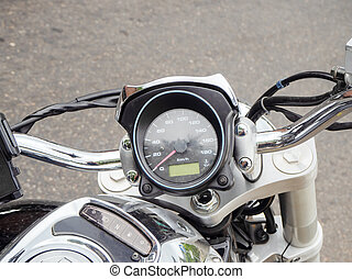 Fragment of a motorcycle steering wheel with round speedometer. Close-up photo