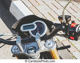 Fragment of motorcycle steering wheel with a round speedometer outdoors. Closeup photo with filter