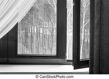 Fragment of a partially open window with curtains