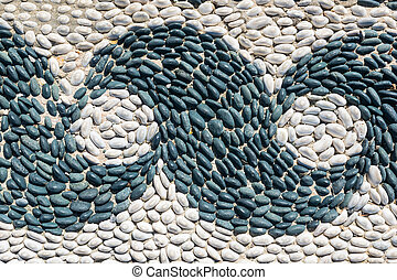 fragment of a pebbled pavement with a pattern of waves
