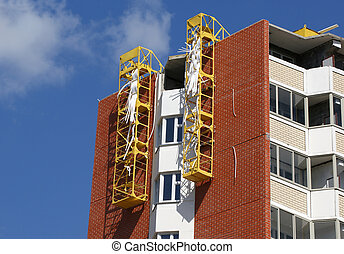 Fragment of a residential apartment building under construction on a background of blue sky