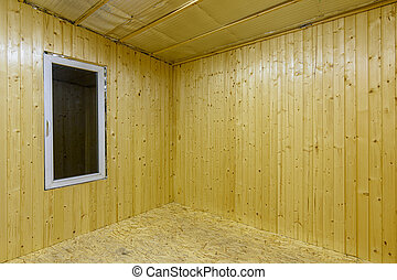 Fragment of a room, finished with wooden clapboard, with a window