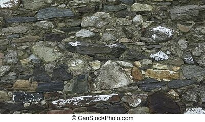Fragment of a stone wall. The old wall is made of stone. Texture or background.