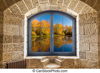 Fragment of a stone wall with a window. Autumn landscape outside the window