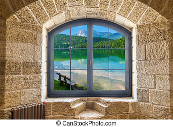 Fragment of a stone wall with a window. Landscape with a lake and a mountain outside the window