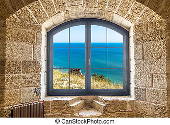 Fragment of a stone wall with a window. Seascape outside the window