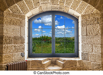 Fragment of a stone wall with a window. Summer landscape outside the window