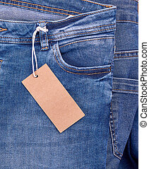 fragment of blue jeans with a brown paper empty tag