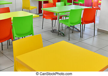 Fragment of interior cafe with bright tables and plastic chairs