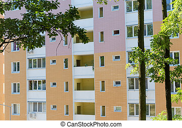 Fragment of multi story apartment building facade, view across trees