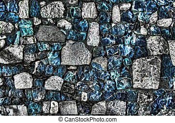 Fragment of old brick wall with river stones texture white grey brown black green blue lime yellow orange maroon violet pink turquoise colored background, different type of stones mosaic surface