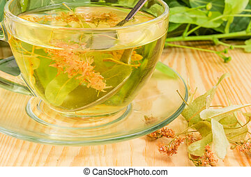 Fragment of transparent glass cup with linden flower tea closeup