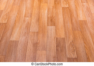 Fragment of indoor floor with new linoleum covering with embossed imitation of parquet pattern, selective focus