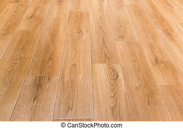 Fragment of indoor floor with linoleum covering with embossed imitation of wooden planks pattern, selective focus