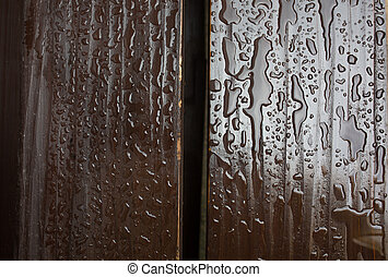 Fragment of wooden bench in the park with water drops
