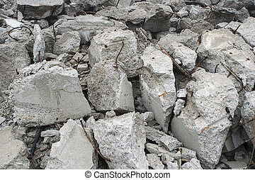 Fragments of concrete slabs in the form of large gray stones with protruding reinforcement. Background