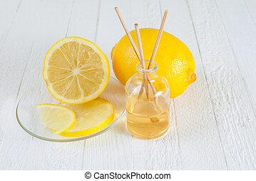 Fragrance sticks or bottle Scent diffuser with Lemon on wooden background.