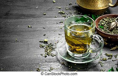 fragrant green tea in a mug. On the black chalkboard