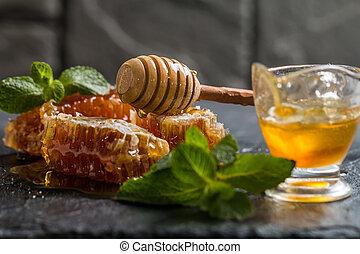 Fragrant honeycomb with honey on dark background