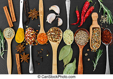 Fragrant seasonings and spices on black background. Top view...