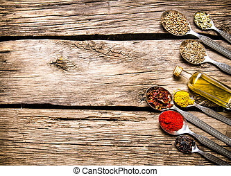 Fragrant spices in spoons with a bottle of olive oil.